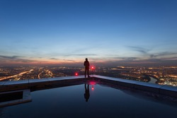 man on the edge of the roof of a skyscraper at night
