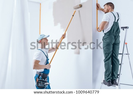 Man on the ladder and painter painting the wall. Home renovation crew concept