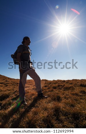 Man on the mountain with sun in frame