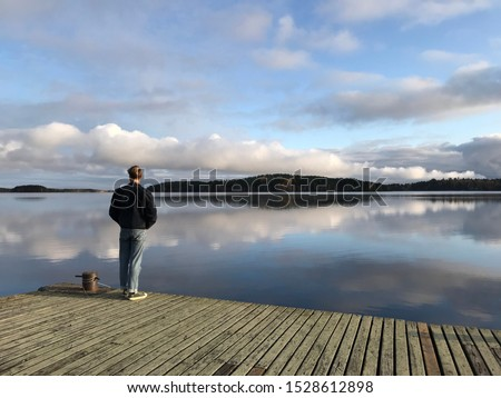 man on the pier. young man stands on a wooden pier on a calm lake on a clear morning. traveler man standing on the lake wooden pier in Finland, Imatra, Mullikoinselka lake