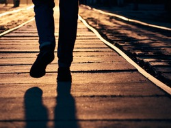 Man on the rails at sunset.
