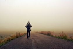 Man on the road in the foggy sunrise