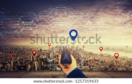 Man on the rooftop holding a mobile phone, blue gps arrow follow the correct way to pointer over big city horizon. Searching location navigation route. Modern technology concept virtual reality maps. #1257319633