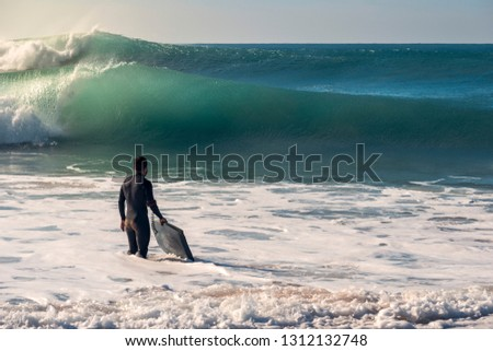 Man on the seashore prepares to surf, wears a black neoprene wetsuit and in his hand has a bodyboard, the water covers him to the knee while watching two huge waves breaking, seawater is turquoise #1312132748