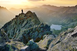 Man on the top of the hill watching wonderful scenery in mountains during summer colorful sunset in High Tatras in Slovakia
