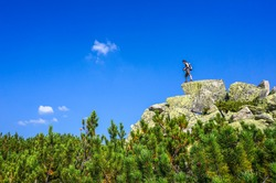 Man on top of a boulder. Background with blue sky
