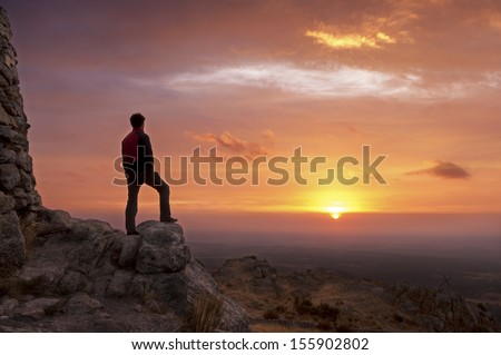 Man on top of a mountain standing contemplates the dawn