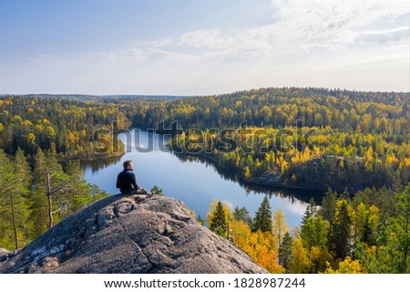 Man on top of a rock in the autumn forest on a background of a beautiful lake. Foto stock ©