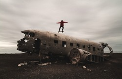 Man on top of an abandoned plane on a skate - Solheimasandur Plane Wreck in Iceland- Adventure wanderer concept
