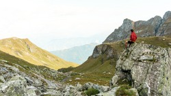 Man on top of mountain, conceptual scene. Hiking in Switzerland. Adventure man Traveler in Mountains. Swiss alps. Hiker or climber on an adventure ascent to the summit of an alpine peak