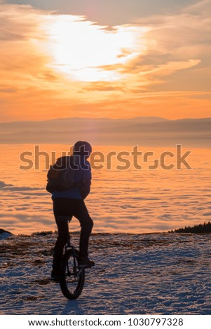 Man on unicycle riding on snowy mountain Schoeckl in Styria, Austria over low stratus fog to sunset #1030797328