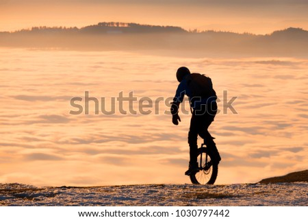 Man on unicycle riding on snowy mountain Schoeckl in Styria, Austria over low stratus fog to sunset #1030797442