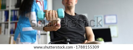 Man on wheelchair holds dumbbell in his hands. Doctor and young man in wheelchair. Treatment and restoration lost functions. Rehabilitation after injuries. Restoration motor functions hand ストックフォト ©