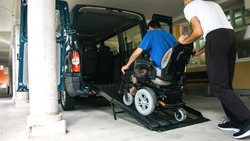 Man on wheelchair using accessible vehicle with ramp for transportation with driver helping.
