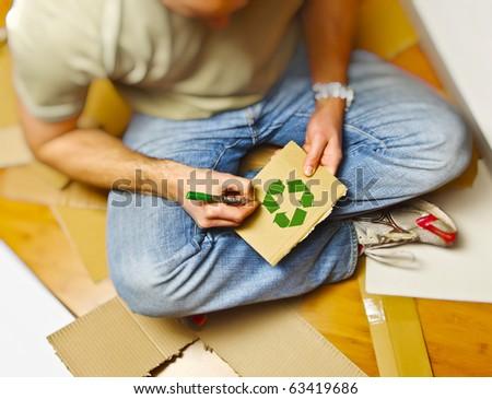 man on wood floor draw recycling symbol on cardboard