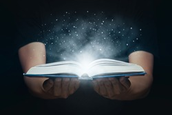 Man opened a magic book with growing lights and magic powder. Learning and education concept.