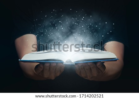 Man opened a magic book with growing lights and magic powder. Learning and education concept. Foto stock ©