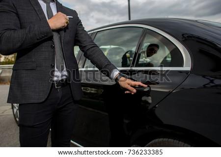Man opening a black car limousines door