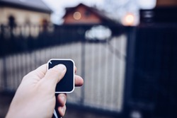 Man opening automatic property gate with remote controller