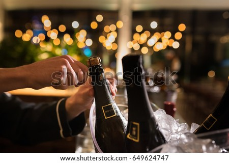 Man opening champagne bottle in a wedding party #649624747