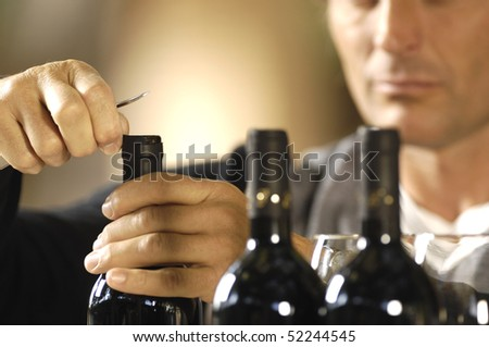 Man opening three bottles of red wine