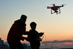 man operating of flying drone at sunset