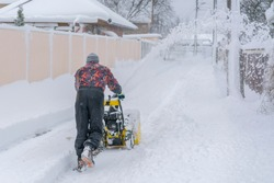 man operating snow blower to remove snow on driveway. A man cleans the road from the snow. Snowy road. snowy winter concept.