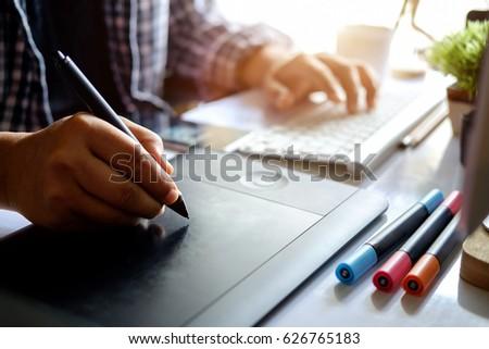 Man or Designer working on digital tablet with Designer stuff on White Desk. Graphic Designer workplace.