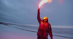 Man or fisherman firing red maritime distress signal flare on winter time. Portrait of male traveler lightening signal or firework torch standing on frozen lake