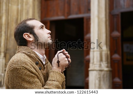 Man or monk praying in front of the church with rosario or prayer beads