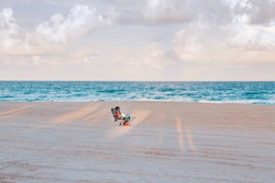 Man or woman sitting in beach chair on empty Hollywood ocean beach in Florida. Senior person enjoying nature water at sunset on seashore coast. View from back. Solo travelling alone outdoors.