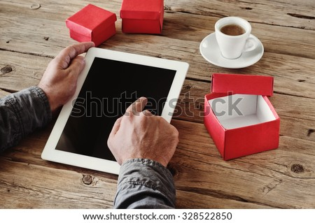 man orders Christmas gifts using a tablet computer via the Internet. Man\'s hand clicks on a blank screen tablet computer