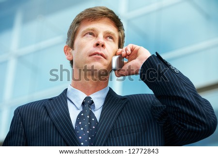 Man outside office building, using cell phone
