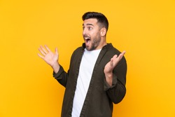 Man over isolated yellow background with surprise facial expression