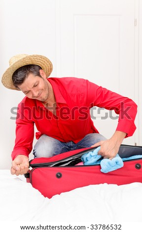 Man packing one's bags wearing a hat being happy for summer vacations holidays ready for take off