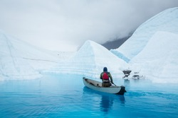 Man paddles a full size inflatable canoe across a deep blue glacier lake carved by water of the melting Matanuska Glacier in Alaska.