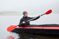 Man paddles red and black kayak with paddle in middle of river or lake in fall season. Autumn and winter kayaking, concentrated man rowing boat in foggy day.
