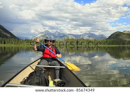 Man paddling a canoe in mountain lake (Vermillion Lakes. Banff National Park, Alberta, Canada)