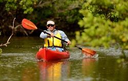 Man paddling in a red kayak in Florida
