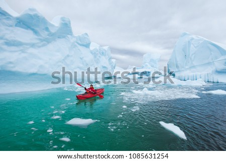 man paddling on kayak between ice in Antractica in Iceberg Graveyard, extreme winter kayaking, polar adventure near Pleneau island #1085631254