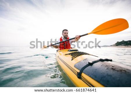 Man paddling sea kayak. Kayaking, adventure, travel, action, healthy lifestyle concept