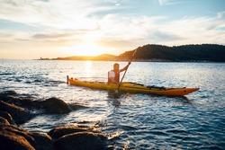 Man paddling the kayak at sunset. Canoeing, kayaking, paddling