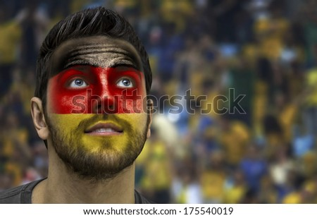 Man painted with german flag on the fans on the stadium