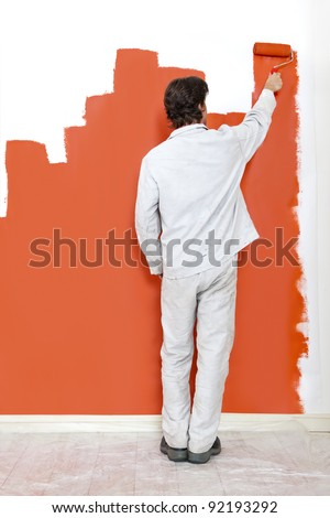 Man, painting a wall with orange paint and a paint roller