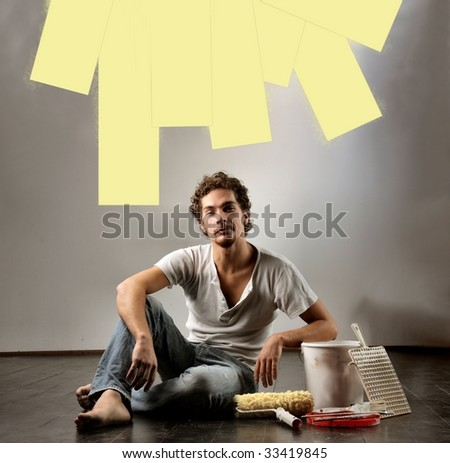man painting on a wall with a roller - stock photo
