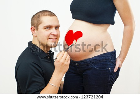 man painting on pregnant woman