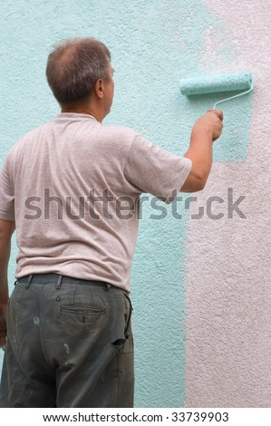 man painting wall with a roll in green outdoor