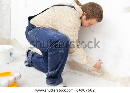 Man painting wall with small roller