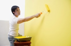 Man painting wall with yellow paint