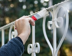 Man painting with brush outdoor fence in white, close up